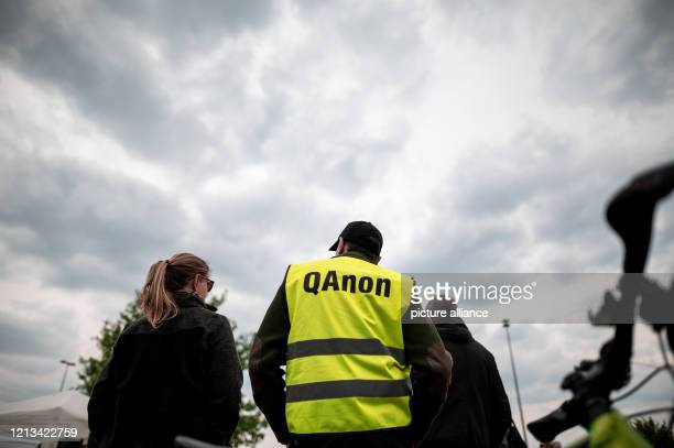 16 May 2020 North RhineWestphalia Essen A participant of the demonstrations against corona measures wears a warning vest with QAnon written on it In...