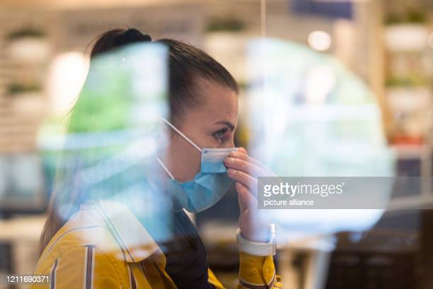 May 2020, Saxony, Dresden: An IKEA customer adviser sits behind a Plexiglas panel in the kitchen department and adjusts her mouthguard. As of today,...