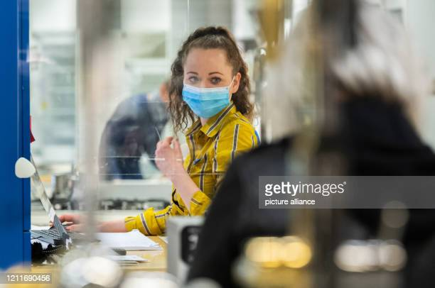 May 2020, Saxony, Dresden: An IKEA customer adviser sits behind a Plexiglas panel in the kitchen department and wears a mouthguard. From today,...