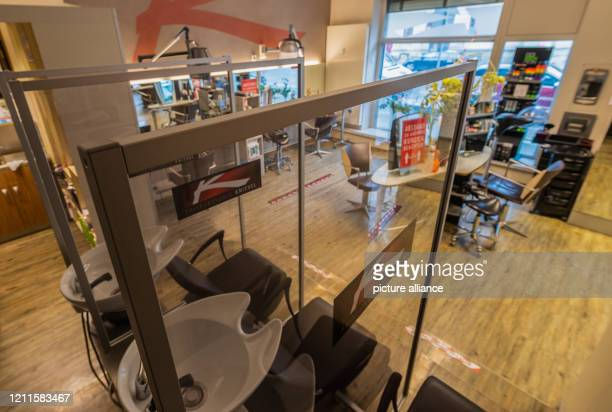 May 2020, Saxony, Dresden: The hair washbasins are separated in a hairdressing studio with Plexiglas panels. After a six-week corona-related break,...