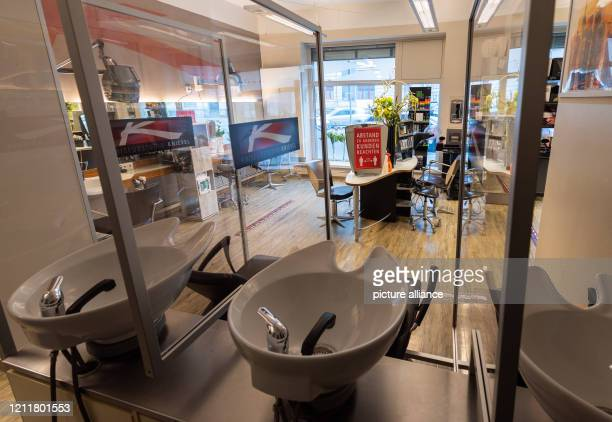May 2020, Saxony, Dresden: The washbasins are separated in a hairdressing studio with plexiglass panels. After a six-week corona-related break,...