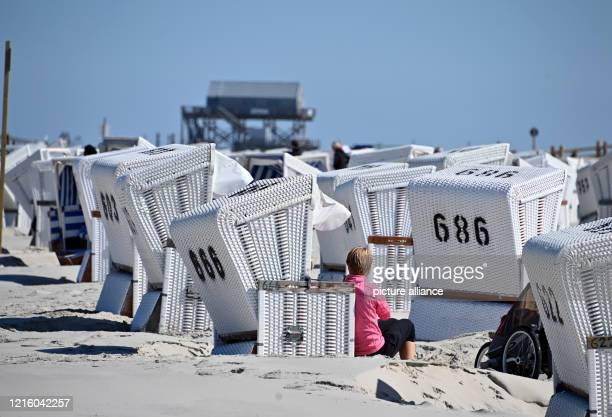 May 2020, Schleswig-Holstein, St.Peter-Ording: Beach chairs can be found at the North Sea beach with blue sky. For the North Frisian islands and...