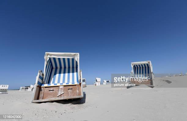 May 2020, Schleswig-Holstein, St.Peter-Ording: Beach chairs can be found on the North Sea beach under a blue sky. For the North Frisian islands and...
