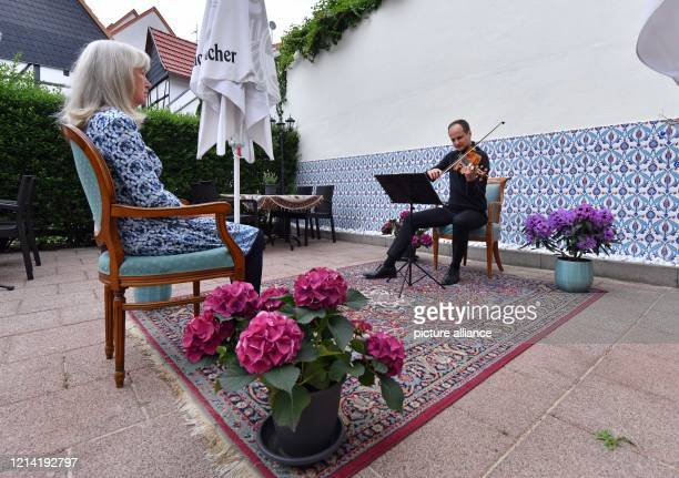 """May 2020, Thuringia, Erfurt: The violinist Joachim Kelber plays in a restaurant in front of the audience Elke Schmidt. With so-called """"1:1 concerts"""",..."""