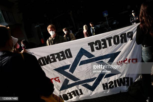 """Numerous people take part in a vigil in front of the synagogue on Fraenkelufer. The action was under the motto """"For Jewish life in Berlin and against..."""