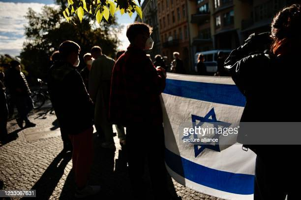 """With an Israeli flag, participants of a vigil stand in front of the synagogue on Fraenkelufer. The action was under the motto """"For Jewish life in..."""