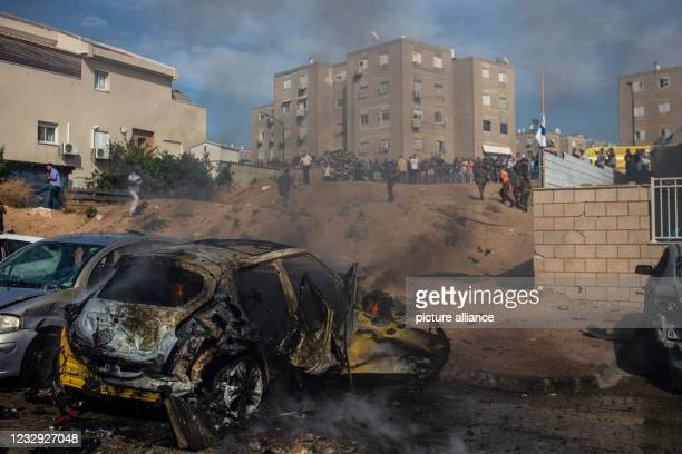 May 2021, Israel, Ashkelon: A general view of a destroyed vehicle caused by a rocket fired from Gaza Strip towards Israel, amid the escalating...