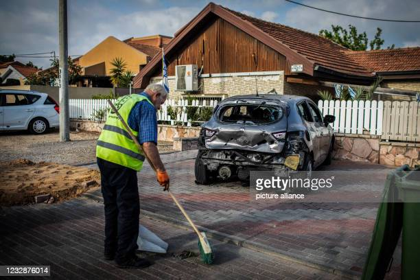 May 2021, Israel, Ashkelon: A worker cleans the floor near a burned car and a covered hole outside a house was hit by a rocket fired from the Gaza...