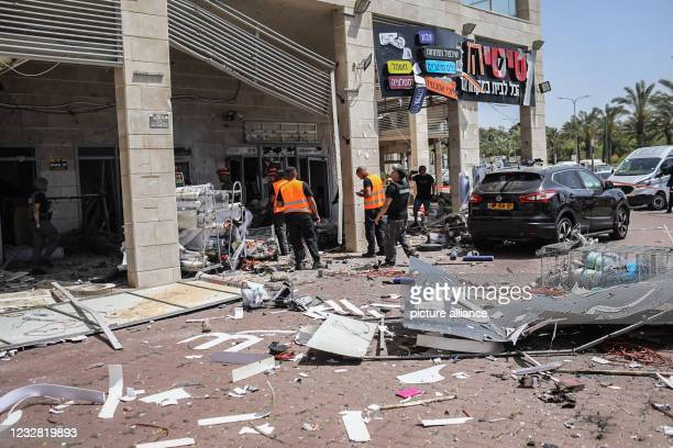 May 2021, Israel, Ashkelon: Members of Israeli security forces inspect a building after being targeted by a rocket fired from the Gaza Strip towards...