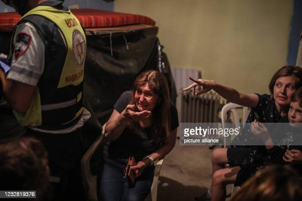 May 2021, Israel, Ashkelon: People sit in a shelter to protect themselves as the city of Ashkelon is targeted by rockets fired from the Gaza Strip....