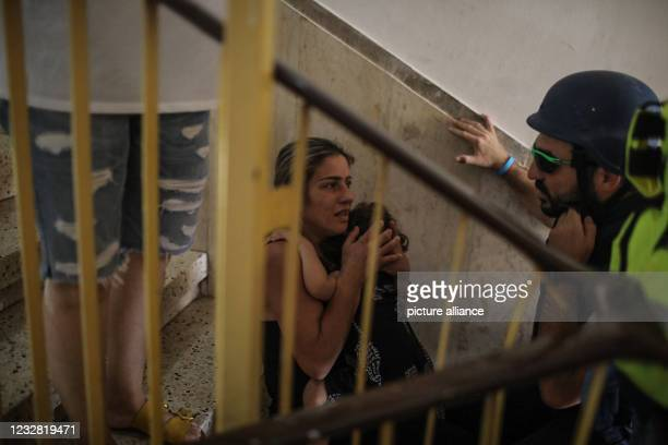 May 2021, Israel, Ashkelon: People sit on the ladder of a house as the city of Ashkelon is targeted by rockets fired from the Gaza Strip. Palestinian...