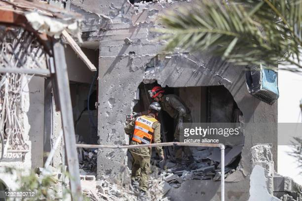 May 2021, Israel, Ashkelon: Rescue workers inspect a damaged building after being hit by rockets fired from the Gaza Strip towards the city of...