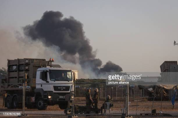 May 2021, Israel, Ashkelon: Thick smoke is seen rising from the premises of the Trans-Israel pipeline, after rockets were fired overnight by the...