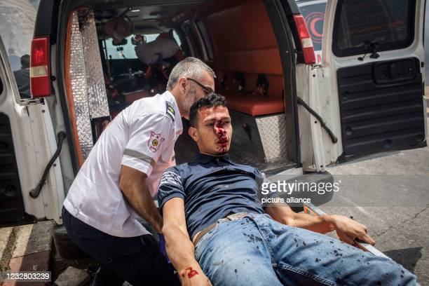 May 2021, Israel, Jerusalem: A Palestinian paramedic transports an injured protester during the clashes between Israeli security forces and...