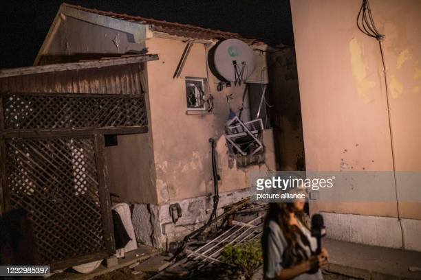 May 2021, Israel, Sderot: A media representative reports in front of a damaged house that was directly hit by a rocket fired from the Gaza Strip amid...