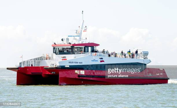"""May 2021, Lower Saxony, Norderney: The catamaran MV """"Adler Rüm Hart"""" is underway in the Wadden Sea off the island of Norderney. AG Reederei..."""