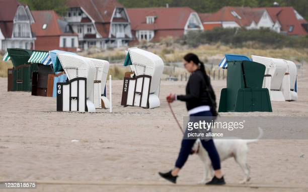 May 2021, Mecklenburg-Western Pomerania, Warnemünde: A woman walks past the few beach chairs with her dog. The big beach chair rentals have not put...