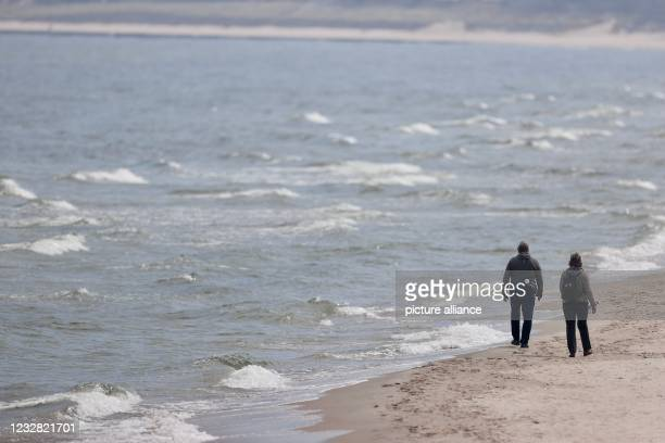May 2021, Mecklenburg-Western Pomerania, Zinnowitz: Only a few walkers are on the beach on the Baltic Sea island of Usedom. The state government of...