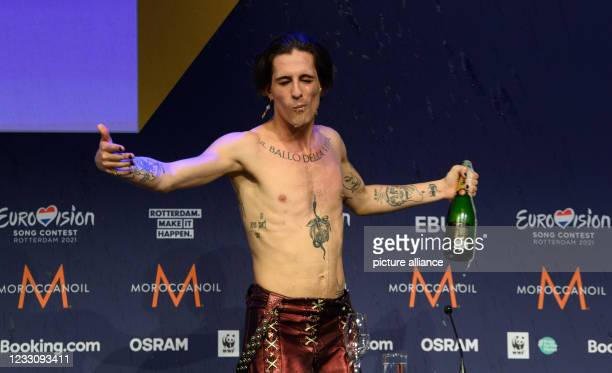 """May 2021, Netherlands, Rotterdam: Singer Damiano from the band """"Maneskin"""" drinks champagne and spreads his arms during a press conference after..."""
