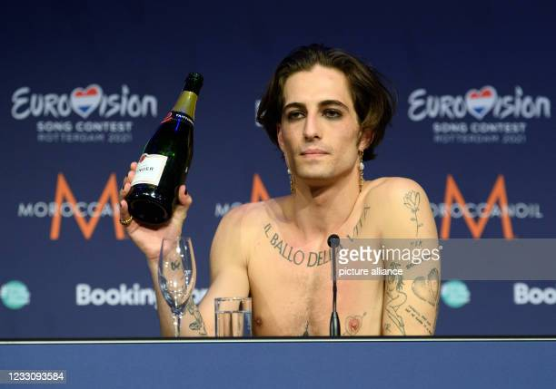 """May 2021, Netherlands, Rotterdam: Singer Damiano from the band """"Maneskin"""" pours himself champagne during a press conference after winning the..."""