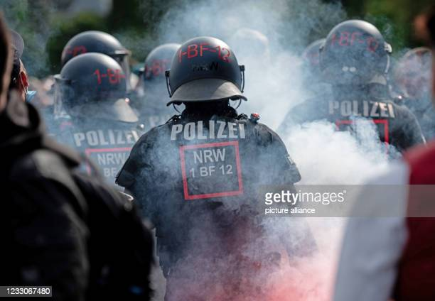 May 2021, North Rhine-Westphalia, Bochum: Police officers stand in the smoke of pyrotechnics as they secure Castroperstraße in front of the Vonovia...