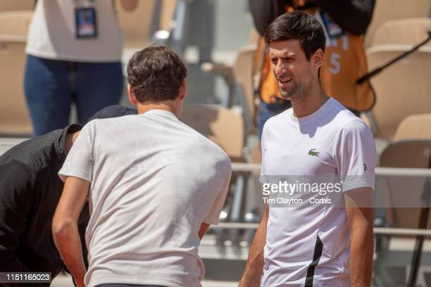 May 23 Novak Djokovic of Serbia and Roger Federer of Switzerland deep in discussion as they cross over training sessions on Court PhilippeChatrier at...