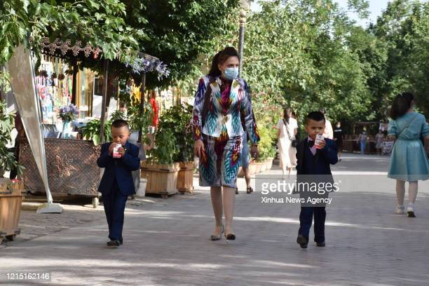 May 24, 2020 -- A woman and two children visit the ancient city of Kashgar in northwest China's Xinjiang Uygur Autonomous Region, May 24, 2020.