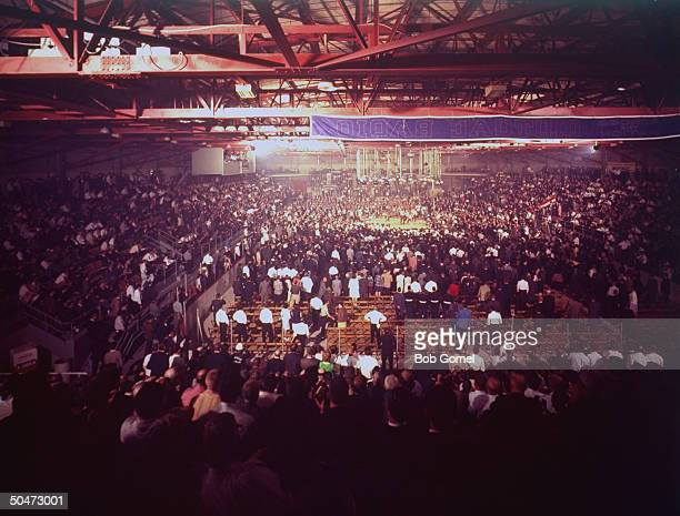 Distant of boxing ring with Muhammad Ali raising his arms during bout against Sonny Liston with fans on their feet watching