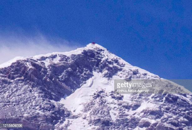 May 27, 2020 -- Chinese surveyors conduct surveying atop Mount Qomolangma in this photo taken with an ultra-telephoto lens on May 27, 2020. A Chinese...