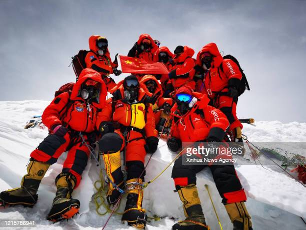 May 27, 2020 -- Chinese surveyors pose for a group photo atop Mount Qomolangma on May 27, 2020. A Chinese surveying team reached the summit of Mount...