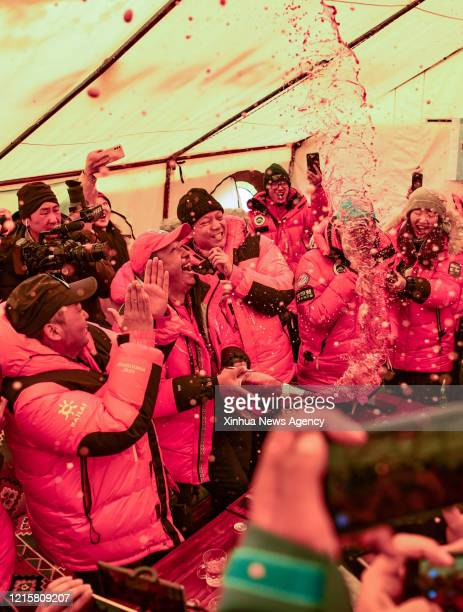 May 27, 2020 -- Staff members celebrate the summiting of Mount Qomolangma by a Chinese surveying team at the Mount Qomolangma base camp in southwest...