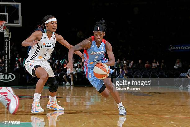 Erica Wheeler of the Atlanta Dream drives past Candice Wiggins of the New York Liberty at the Madison Square Garden on May 27 2015 in New York New...