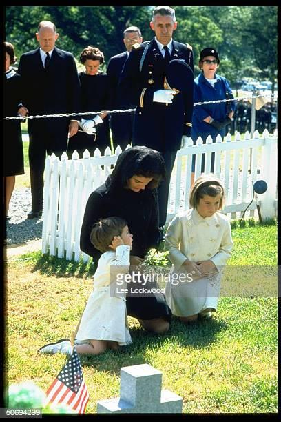 Jacqueline Kennedy w children John Jr and Caroline kneeling in prayer at grave site of slain President on his first birthday after assassination w...