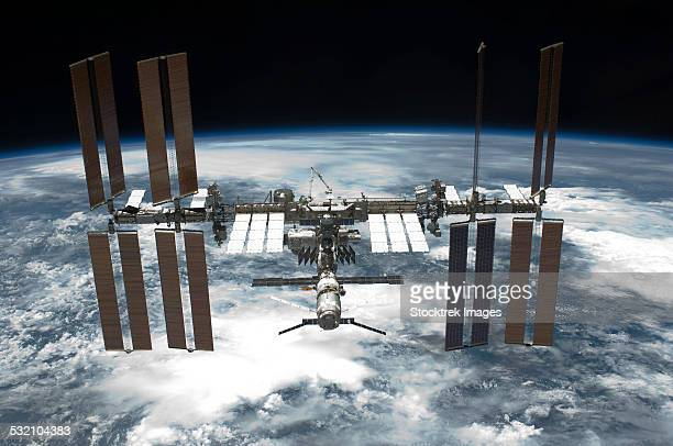 may 29, 2011 - the international space station backdropped by a blue and white earth. - international space station stock pictures, royalty-free photos & images