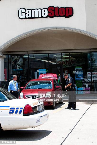 Sheriff officer's exam a crime scene in front of the GameStop while one person is dead in the red Nissan in the North Shore suburb of Houston A