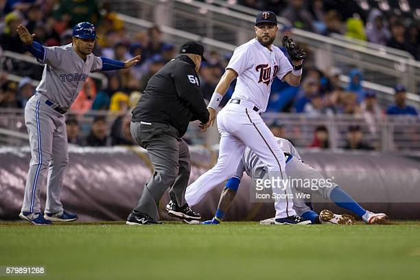 May 29 2015 at Minnesota Twins infielder Trevor Plouffe turns to third base umpire Eric Cooper as third base coach Luis Rivera signals that Toronto...