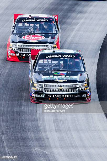 Ben Rhodes driver of the Alpha Energy Solutions Chevy truck and Ron Hornaday Jr driver of the Rheem Chevy truck race out of turn 2 during the Camping...