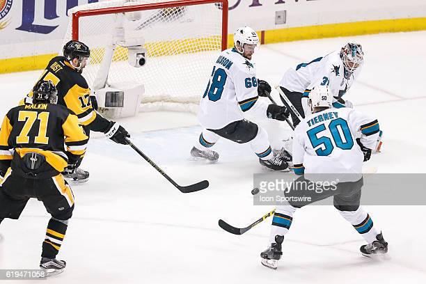 Pittsburgh Penguins right wing Bryan Rust prepares to shoot loose puck as San Jose Sharks right wing Melker Karlsson San Jose Sharks center Chris...