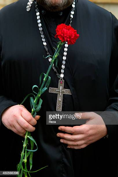 May 9 Martyrs Lane, Baku, Azerbaijan. A representative of the Russian Orthodox Church brings a red carnation to Martyrs Lane, a cemetery and memorial...