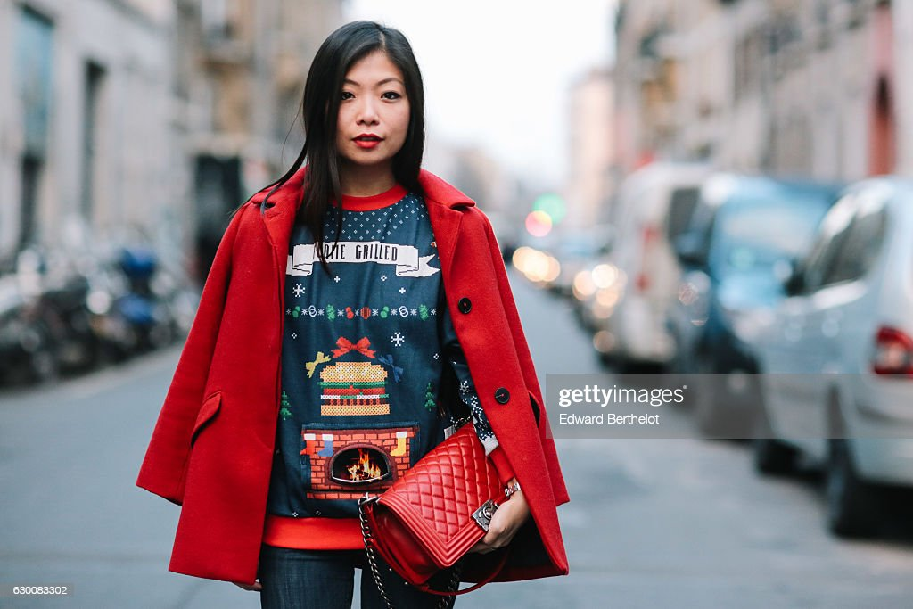 May Berthelot, fashion and life style blogger, is wearing a Rad x Burger King Christmas sweater featuring an animated grill fire on the front with the use of a specific iphone application, New Look black shiny boots, H&M denim jeans, a Zara red long coat, and a Chanel Boy bag, on December 16, 2016 in Paris, France.