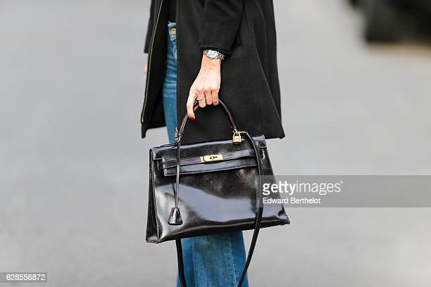 May Berthelot fashion and life style blogger wears a black long coat designed by herself Levi's flared blue denim jeans a Chanel black cashmere body...