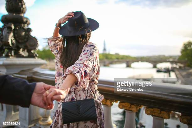May Berthelot fashion blogger and Head of Legal at Videdressingcom wears a Magali Pascal floral print dress a New Look hat Zara black boots and a...