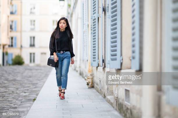 May Berthelot fashion blogger and Head of Legal at Videdressingcom wears a Harpe black lace top The Kooples blue denim cropped jeans a Gucci belt a...