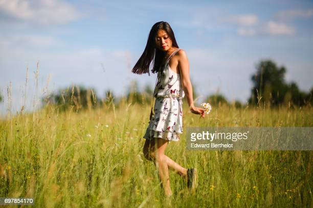 May Berthelot fashion blogger and Head of Legal at Videdressingcom wears a The Kooples white lace flower print dress and Zara shoes in a straw field...
