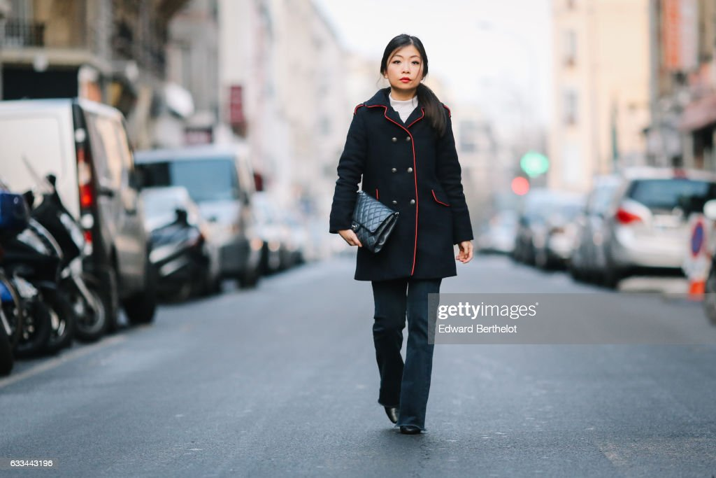 May Berthelot, Head of Legal at Videdressing.com and fashion blogger, is wearing Newlook denim jeans, a Zara military officer coat, a Chanel bag, a Courreges white top, and Zara boots, on February 1, 2017 in Paris, France.