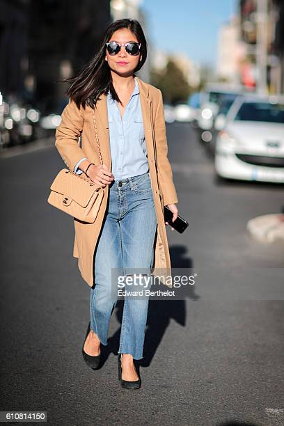 May Berthelot is wearing a Chanel timeless bag Maje blue denim jeans a Topshop shirt a tailored camel coat vintage shoes and TIJN sunglasses in the...