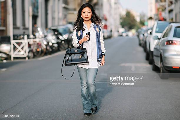 May Berthelot , is wearing a Hermes Kelly black bag, a Zara white and blue bomber jacket, a Topshop white shirt, and Diesel blue flare denim jeans,...