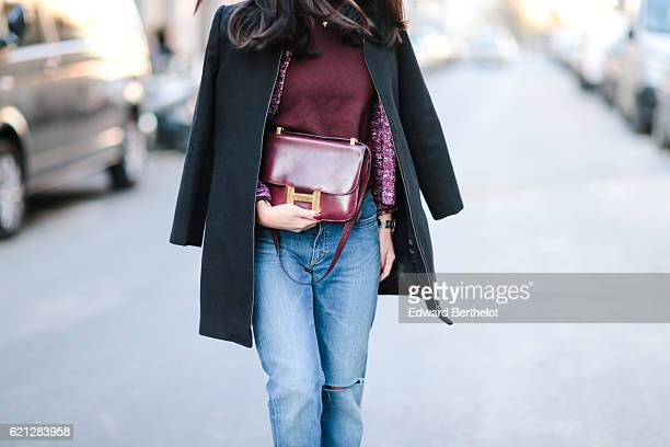 May Berthelot is wearing a Hermes red turtleneck top a 9Avril necklace Maje blue denim jeans Marks and Spencer Burgundy boots an Isabel Marant jacket...