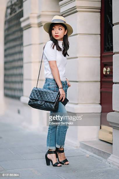 May Berthelot is wearing a Maison Michel yellow hat a Courreges white turtleneck top The Kooples blue denim boyfriend jeans HM sandals and a Chanel...
