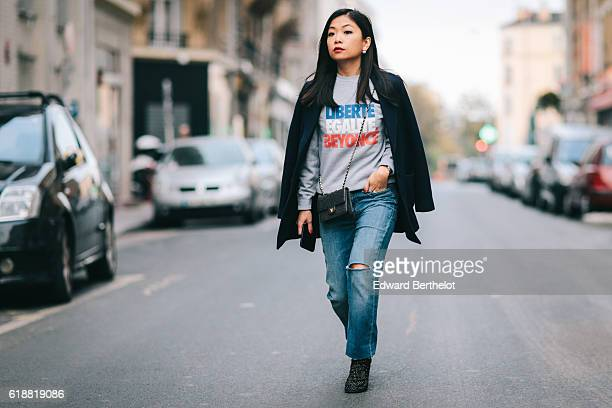May Berthelot is wearing a RAD gray sweater with the inscription 'Liberte Egalite Beyonce' Maje blue denim jeans a blue coat designed by herself...